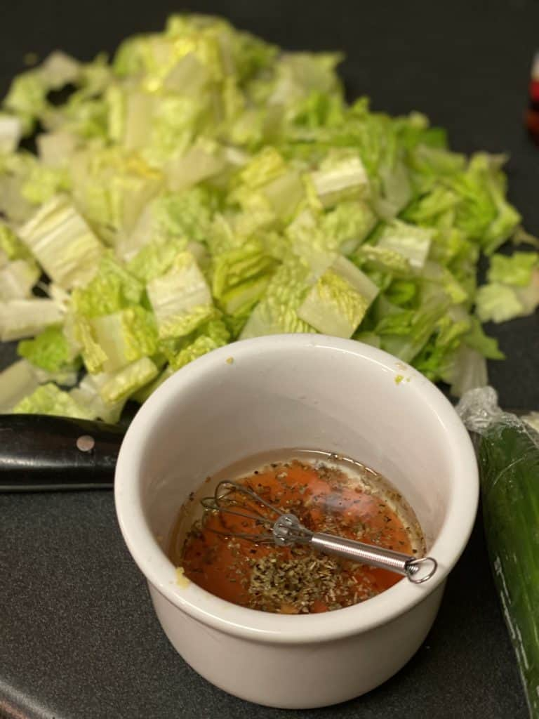 a bowl of Greek dressing and a plate of chopped romaine lettuce