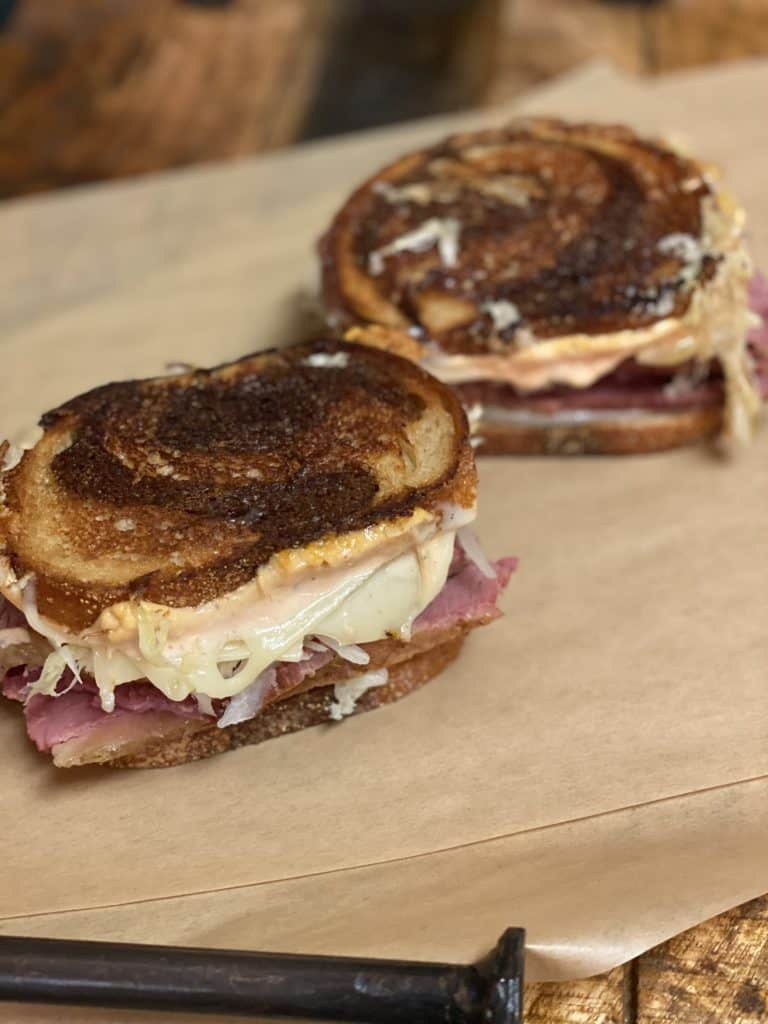 two rueben sandwiches on brown parchment paper