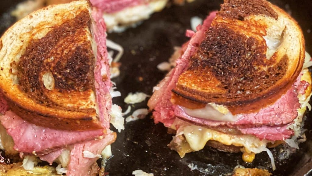 three halves of a rueben sandwich toasting in a cast iron pan