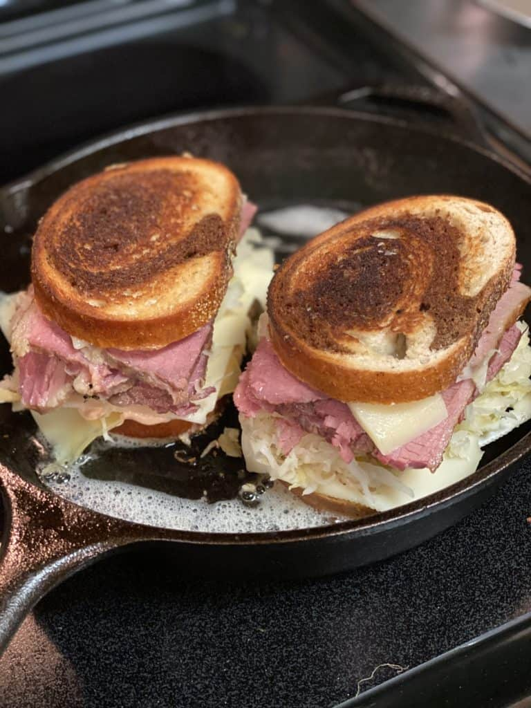 two rueben sandwiches toasting in a cast iron pan