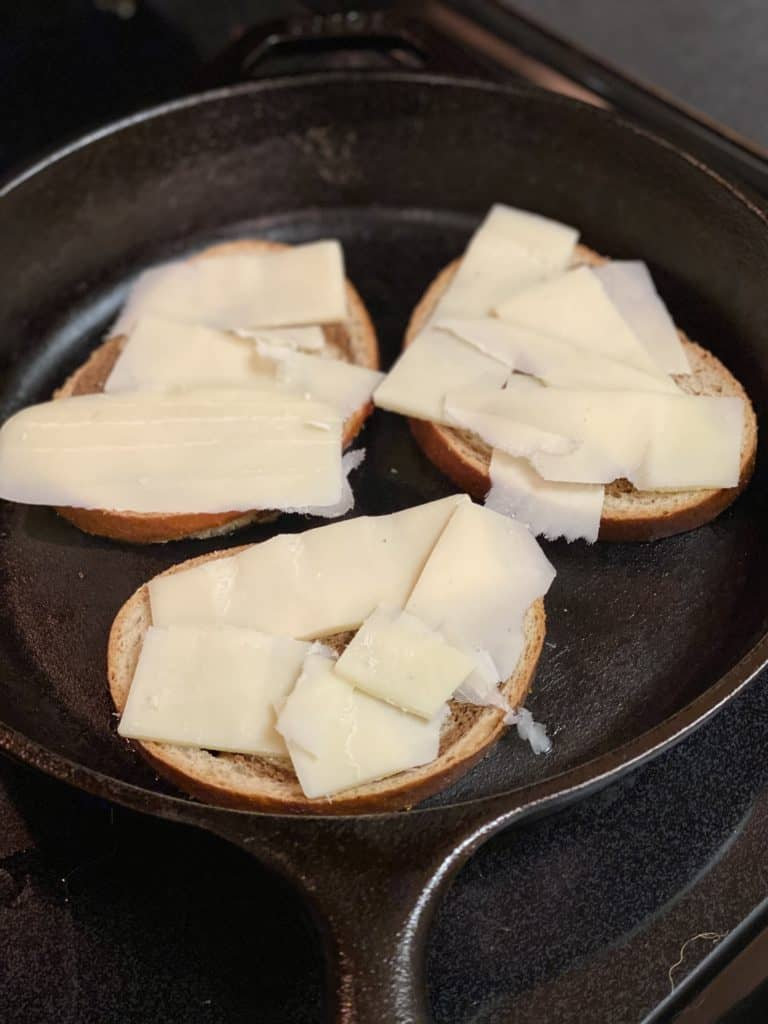 three slices of bread in a cast iron pan topped with Gruyere cheese slices