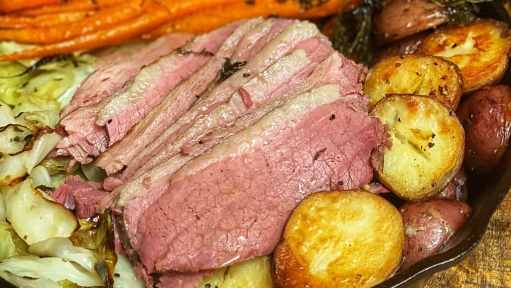 a cast iron pan of corned beef, cabbage, carrots, and potatoes