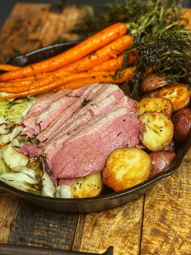 a cast iron pan full of corned beef slices, roasted potatoes, carrots and cabbage