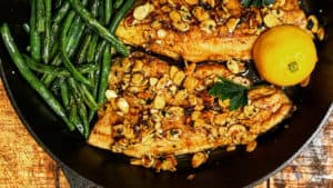 a cast iron pan of seared trout with green beans, lemons, and almonds