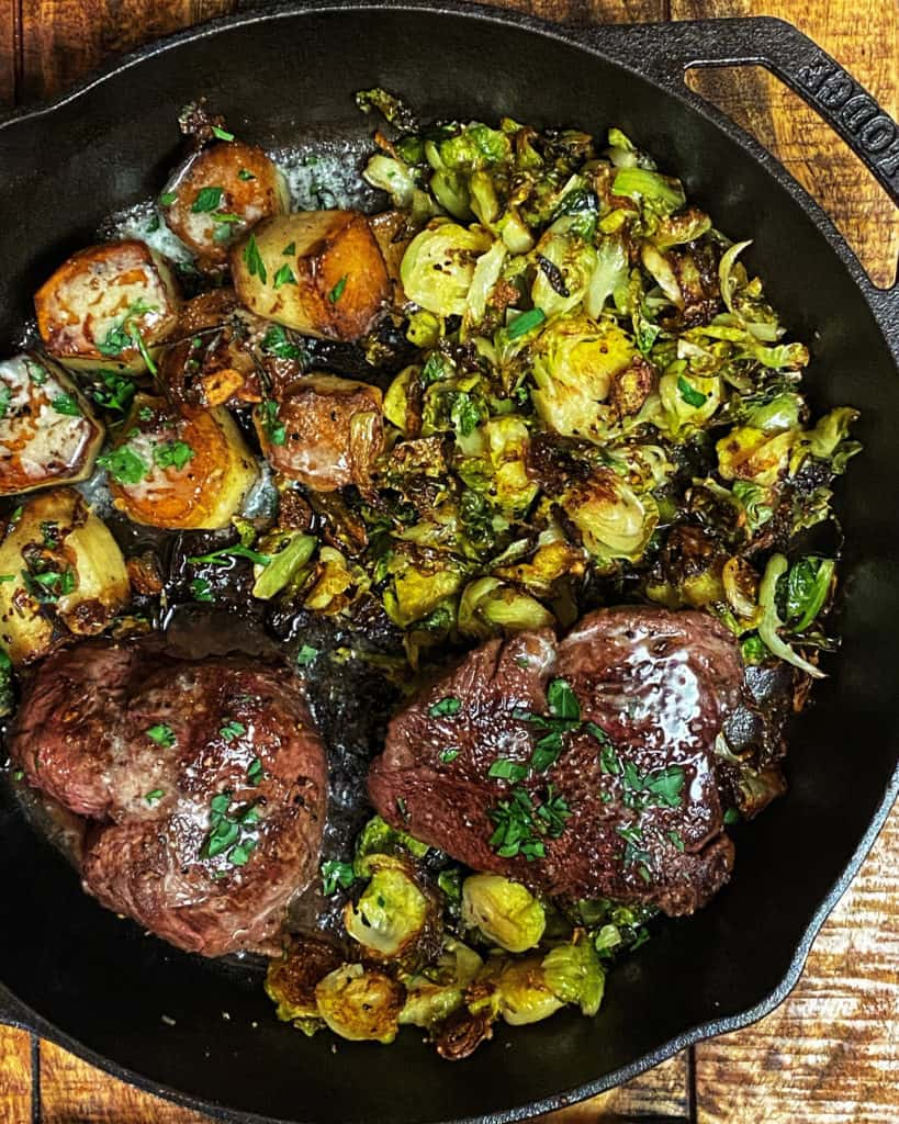 a cast iron pan of steak, potatoes, and Brussels sprouts