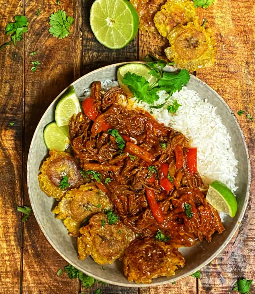 a bowl of rice with ropa vieja and tostones