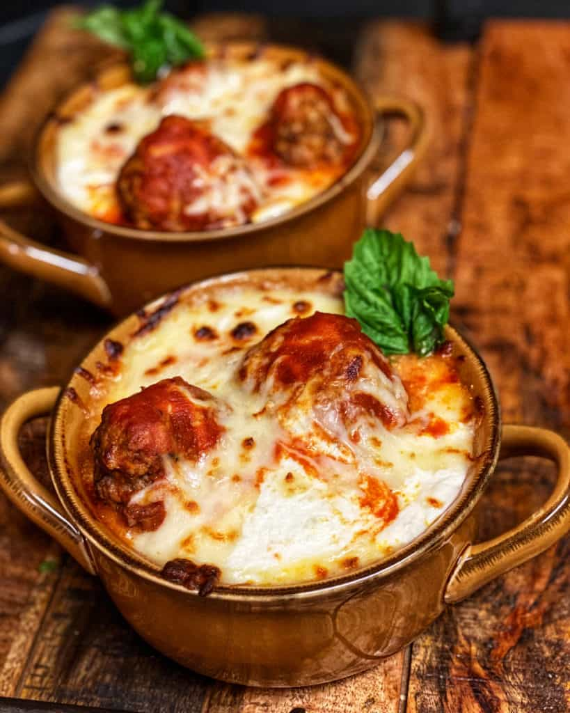 two bowls of baked meatballs garnished with basil