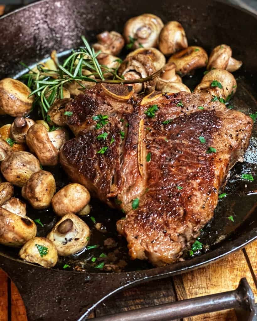 seared porterhouse steak in a cast iron pan with mushrooms, garlic and rosemary