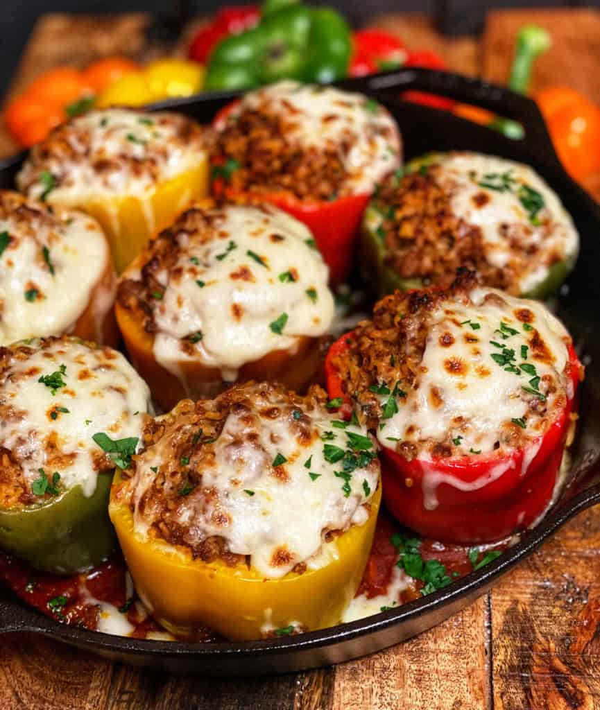 eight stuffed bell peppers in a cast iron pan