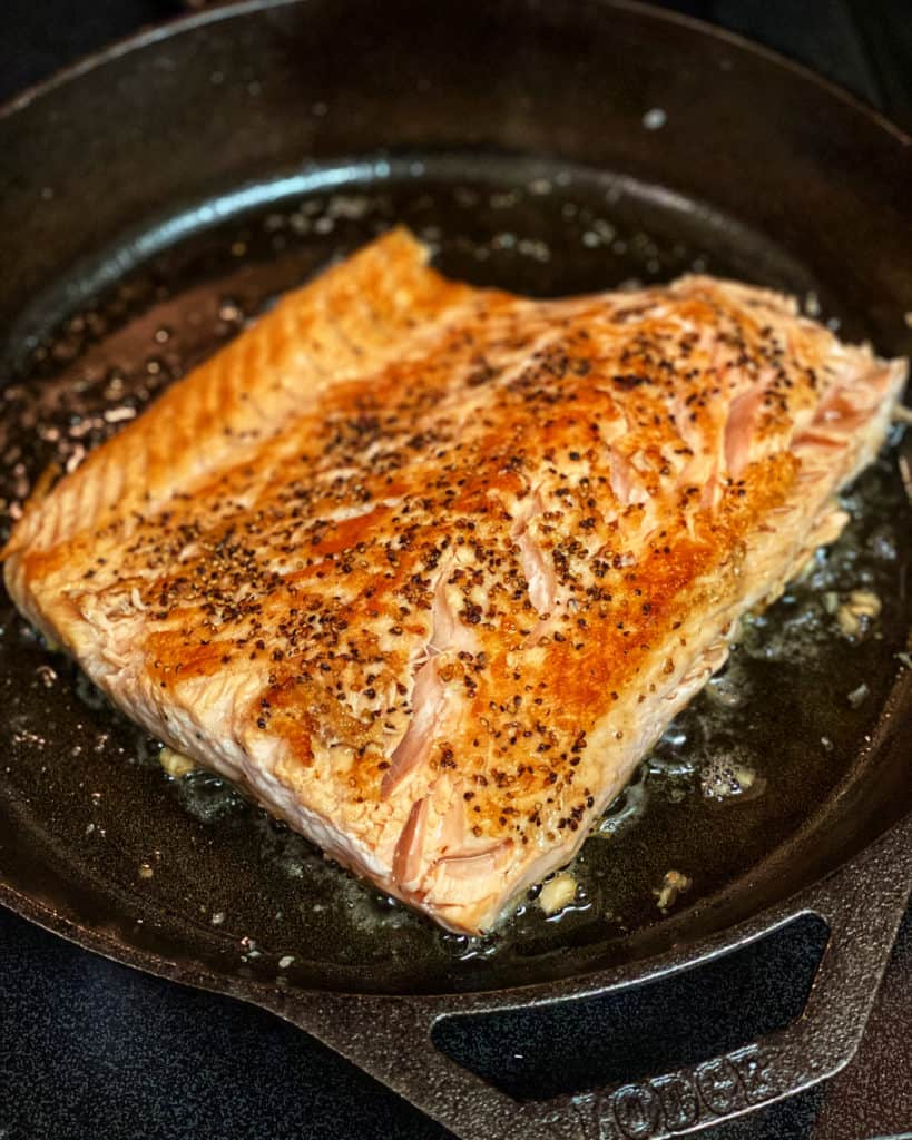 salmon seared in a cast iron pan for pan seared salmon in a coconut cream sauce
