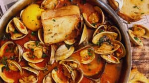 a pan of clams with chorizo in a tomato broth with toasted bread