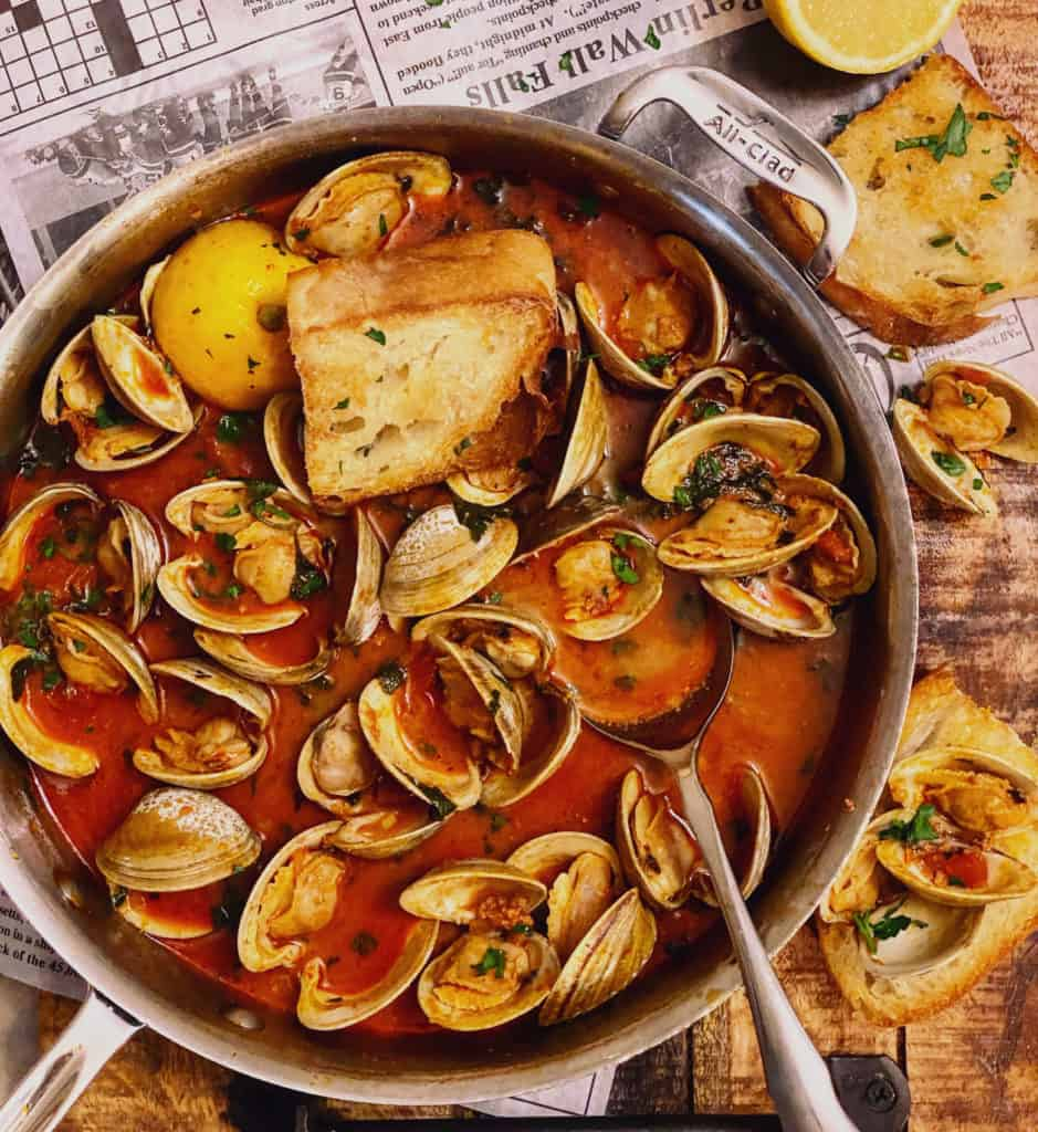 a pan of clams with chorizo in a tomato broth