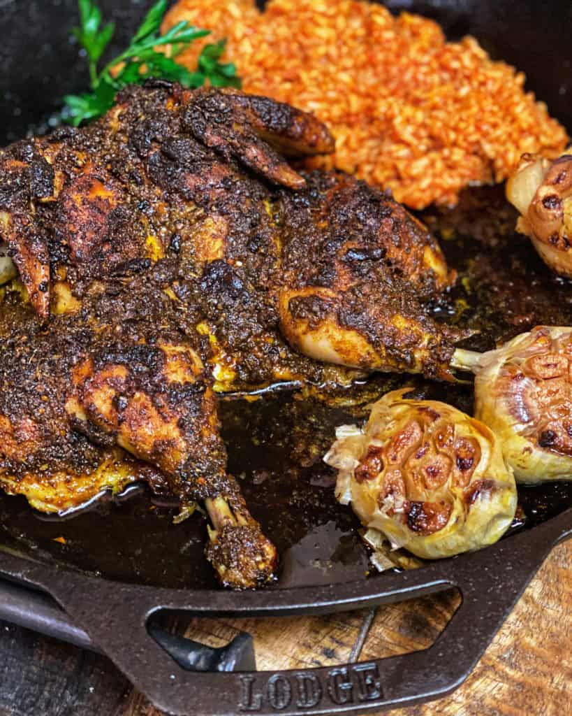spatchcock chicken with a side of Jollof rice and three roasted garlic bulbs