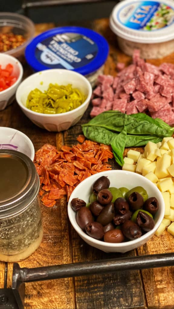 ingredients for the best pasta salad in bowls on a wooden board