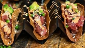 six wonton tuna tacos in taco holders on a wooden display board