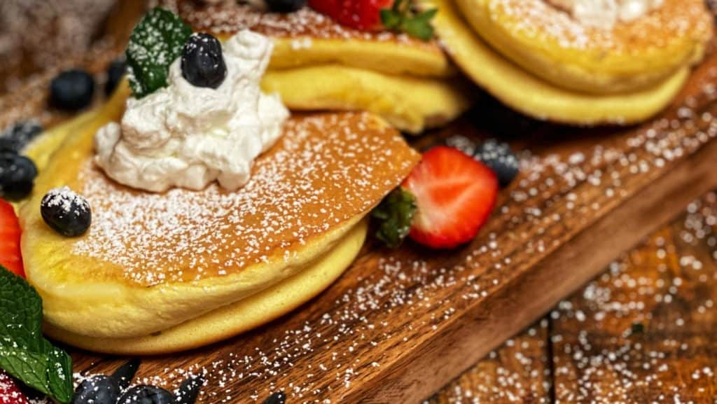 three Japanese soufflé pancakes on a wooden board topped with strawberries, blueberries, powdered sugar and whipped cream