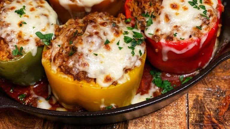 side view of eight colored stuffed bell peppers in a cast iron pan with cheese browned and melting