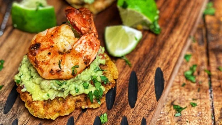 three tostones topped with guacamole and blackened shrimp on a wooden board