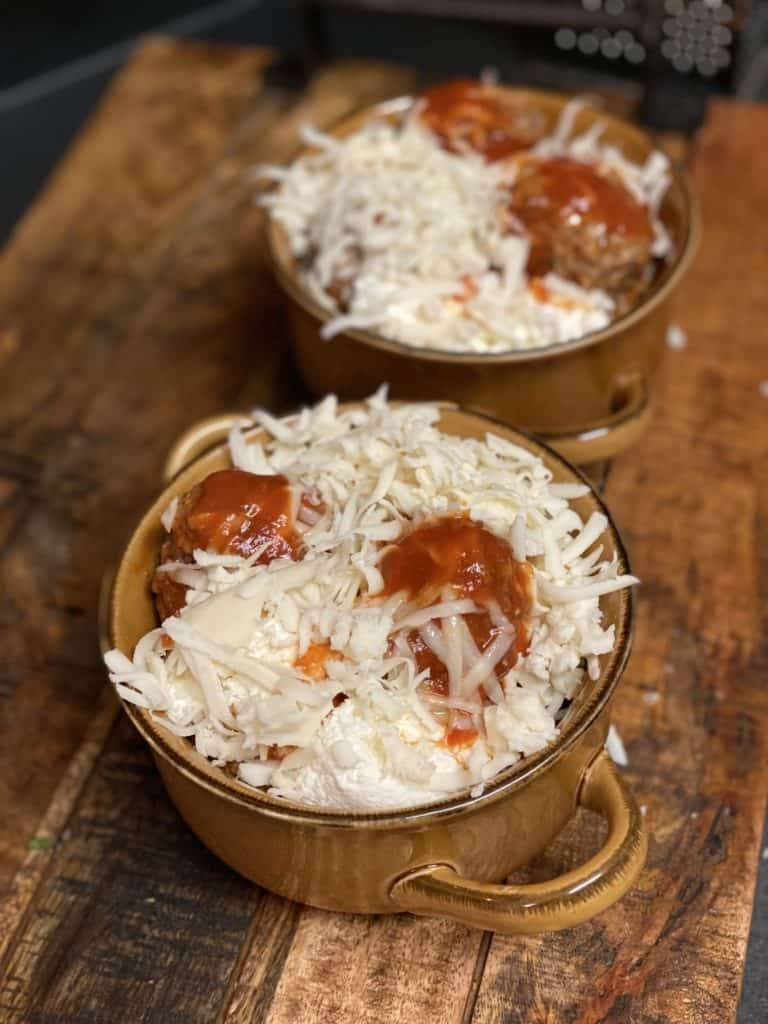 two bowls of meatballs covered with shredded cheese for my Baked Meatballs recipe
