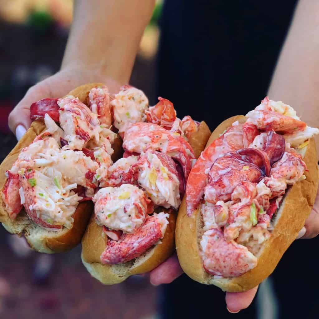 me holding three of the best lobster rolls in my hands