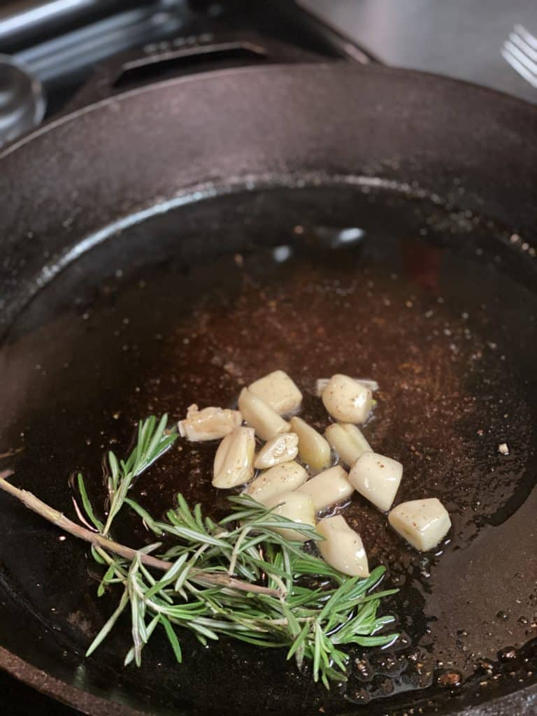 garlic and rosemary in a cast iron pan
