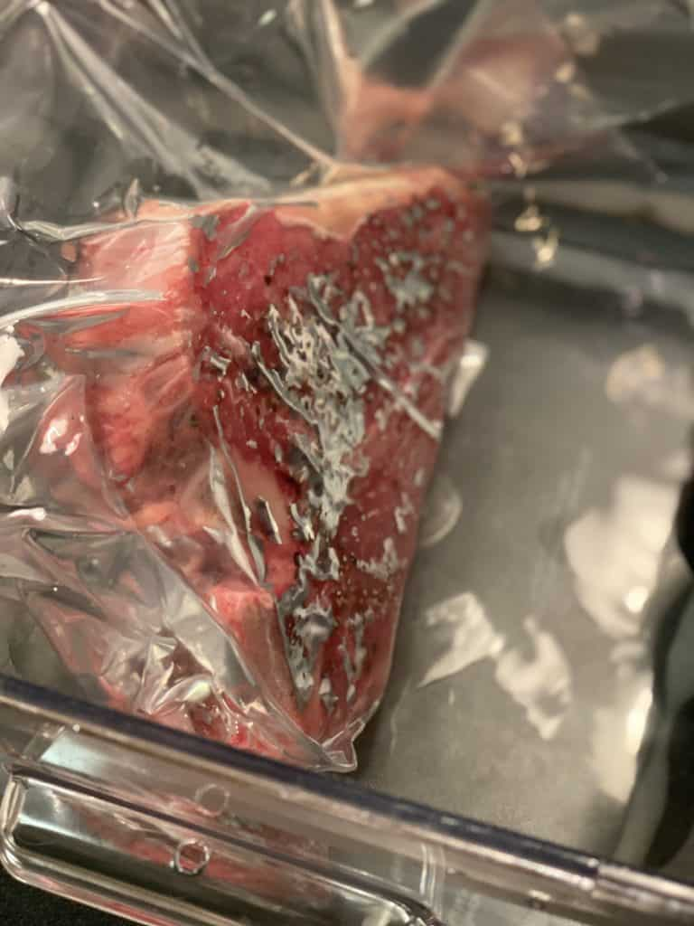 a porterhouse steak in a sealed bag in a sous vide