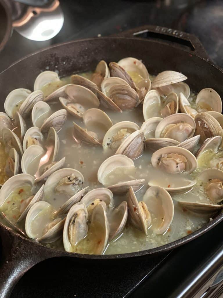 butter garlic steamed clams opened in a cast iron pan with broth