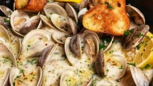 a cast iron pan of butter garlic steamed clams with bread