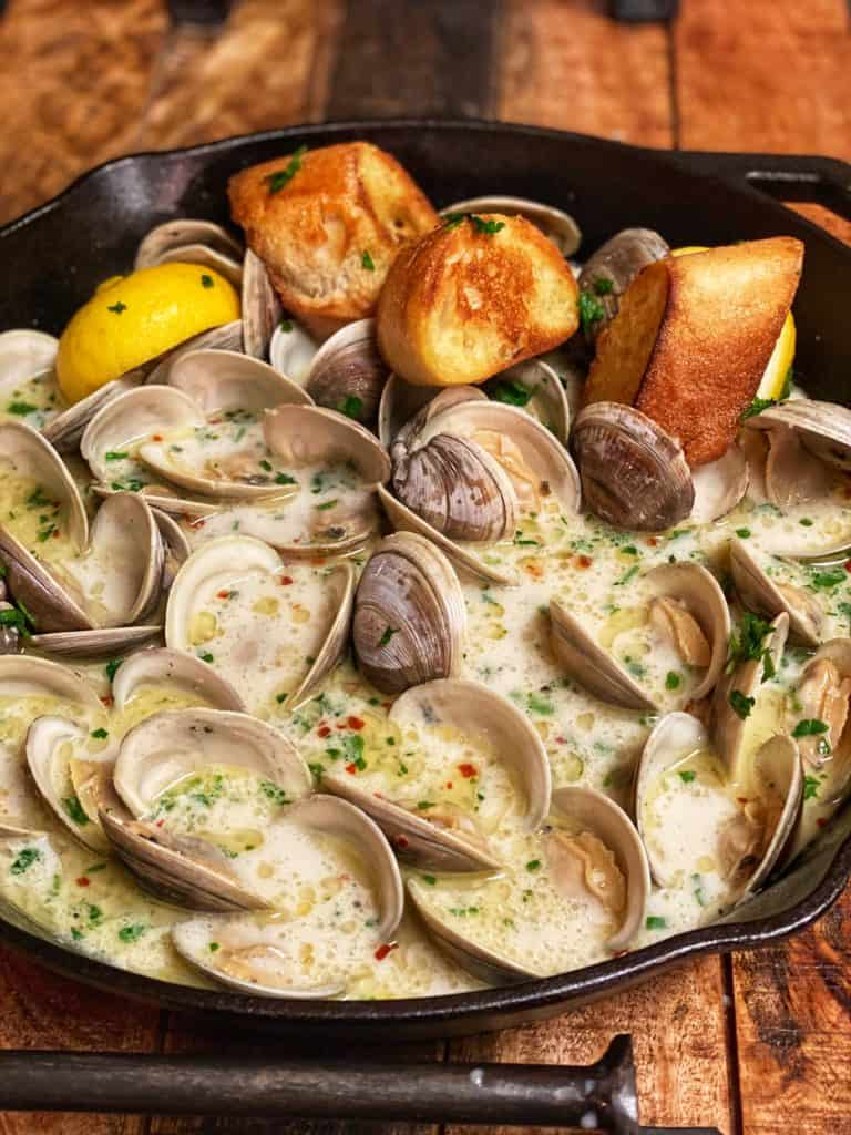 a cast iron pan of butter garlic steamed clams with bread and lemons