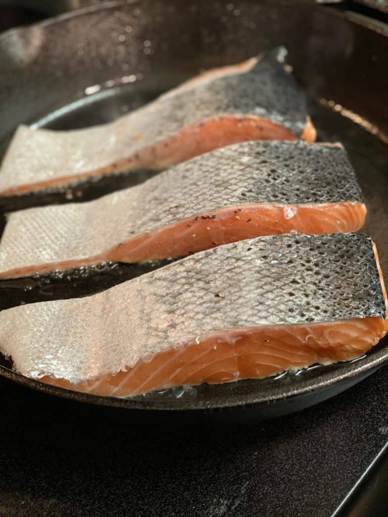 three filets of salmon searing skin side up in a cast iron pan