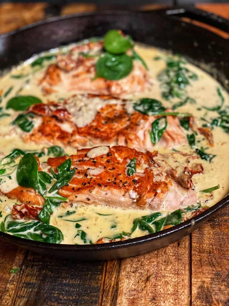 a cast iron pan of salmon in a creamy spinach sauce