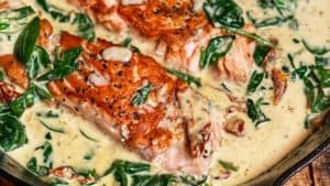 a cast iron pan of creamy tuscan sauce with three seared filets of salmon and spinach