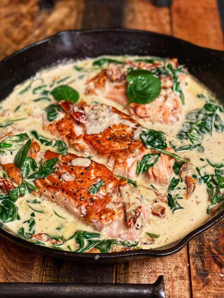 a cast iron pan of creamy tuscan sauce with three seared filets of salmon