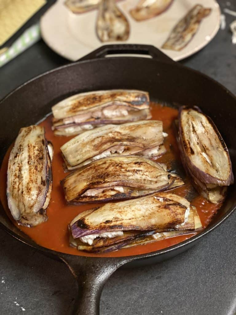six eggplant stacks filled with ricotta cheese and layered on top of sauce in a cast iron pan