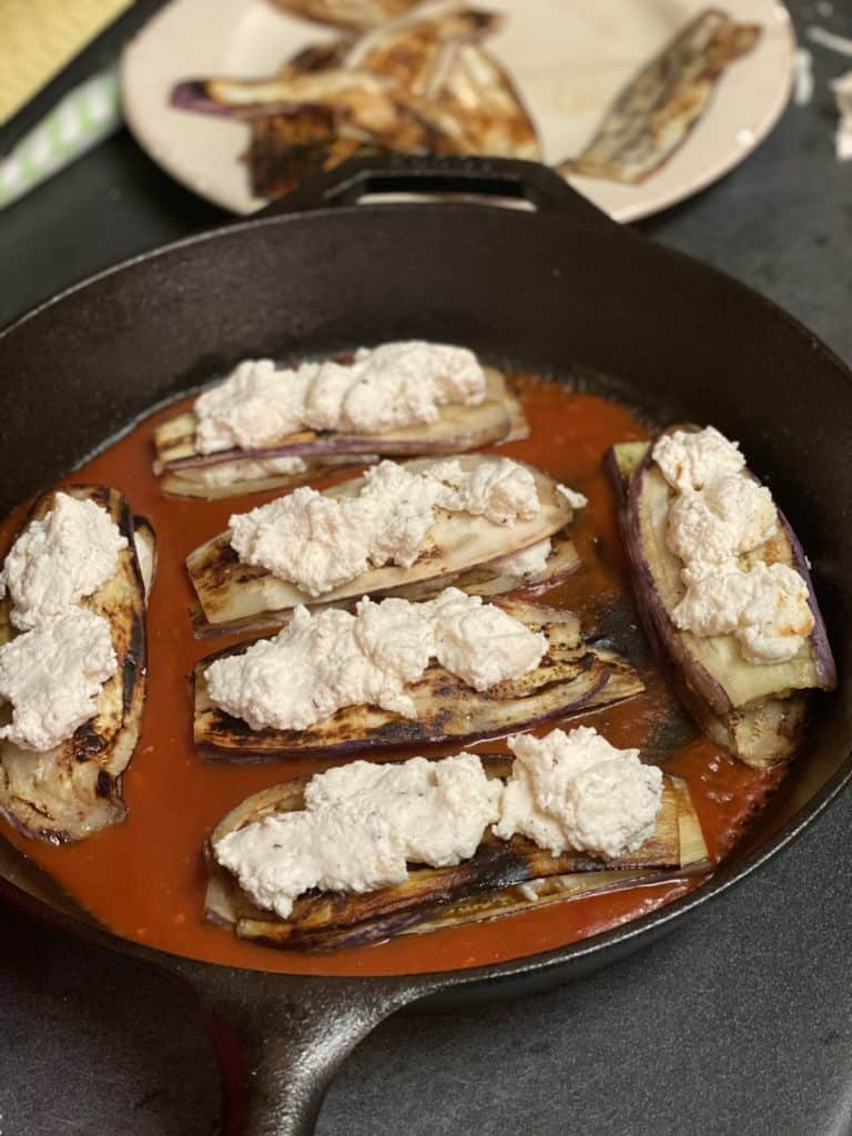 six eggplant slices topped with ricotta cheese in a cast iron pan with sauce