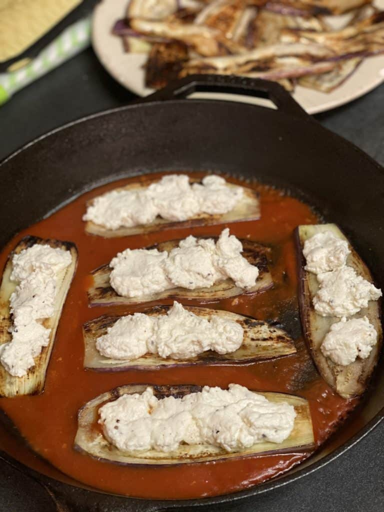 six eggplant slices in a cast iron pan on top of a layer of sauce topped with ricotta cheese