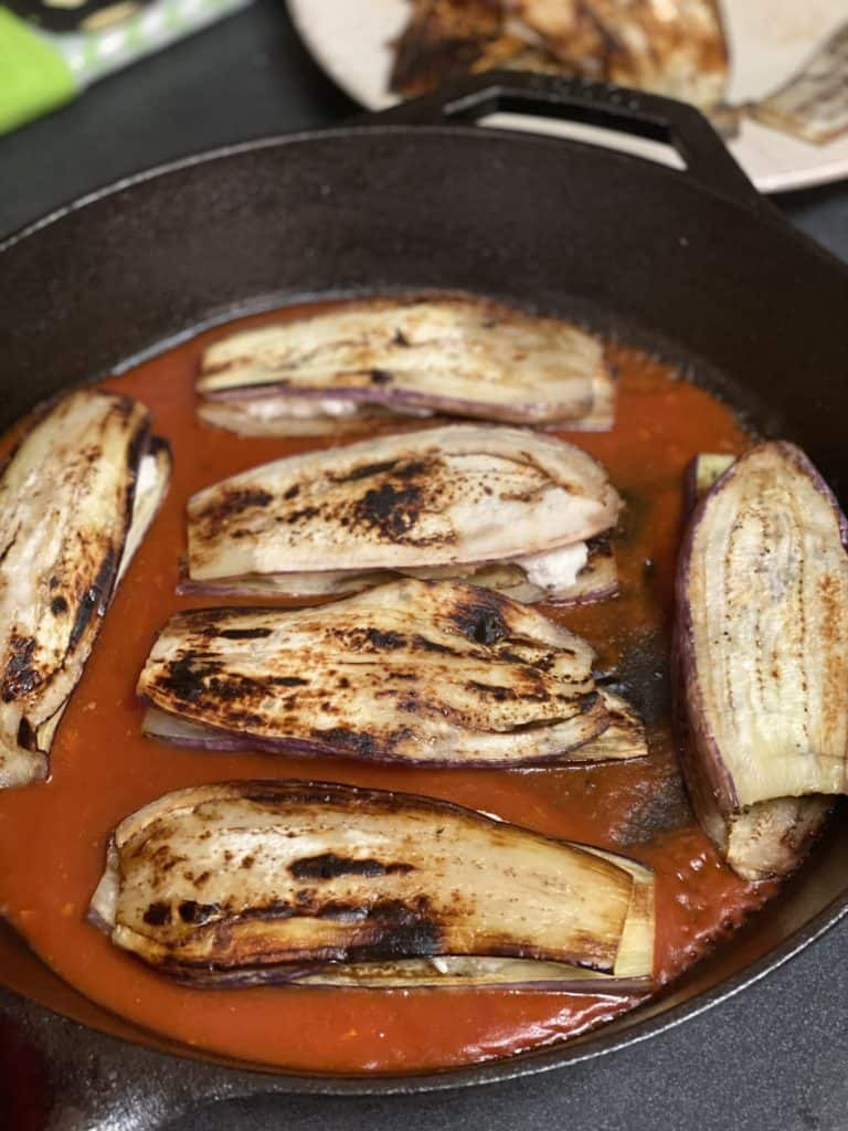 six eggplant slices in a cast iron pan on top of a layer of sauce