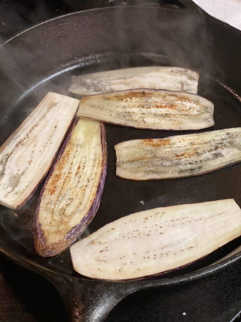 six eggplant slices sautéing in a cast iron pan