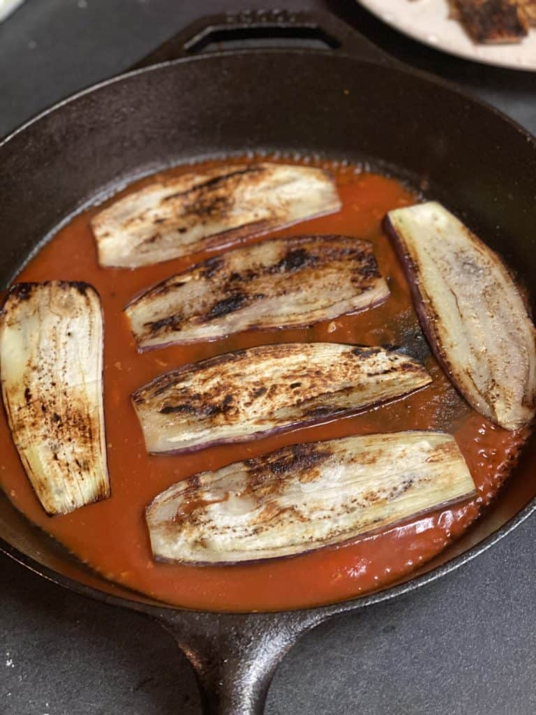 six sautéed eggplant slices on top of sauce in a cast iron pan