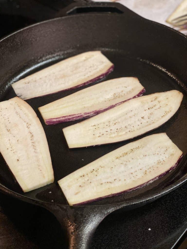 five eggplant slices sautéing in a cast iron pan
