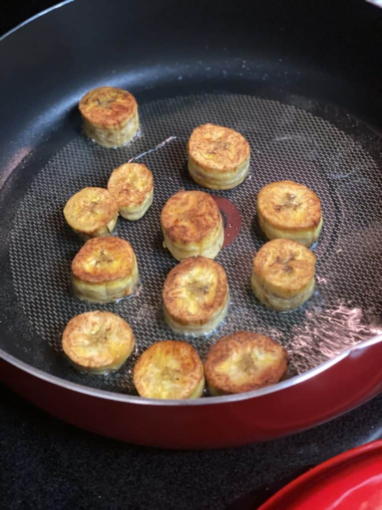 plantain circles frying in a non-stick pan for Tostones