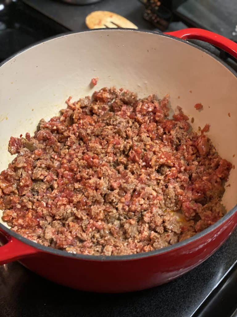 hot sausage crumbled and browning in an enameled cast iron pan