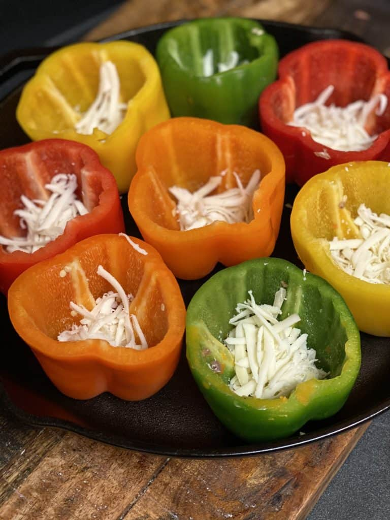 eight colored bell peppers filled with shredded mozzarella at the bottom