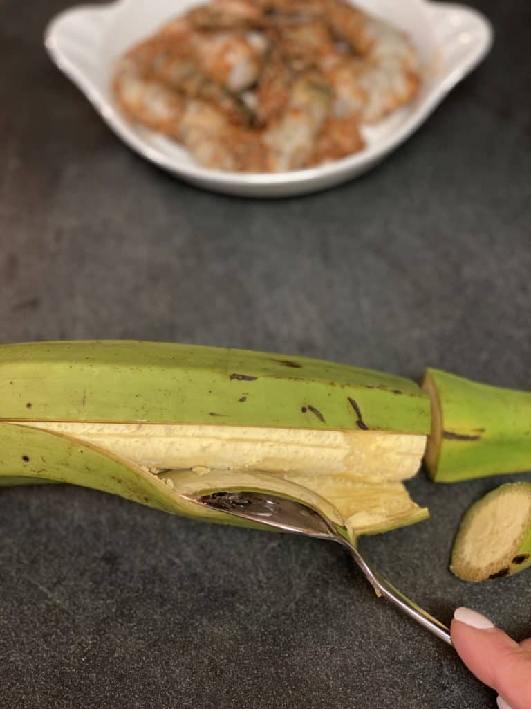 one plantain being peeled with a spoon