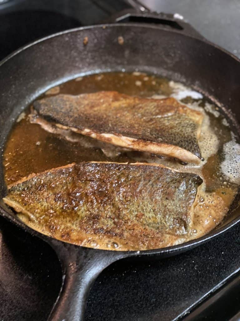 two filets of trout searing in a cast iron pan flesh side down