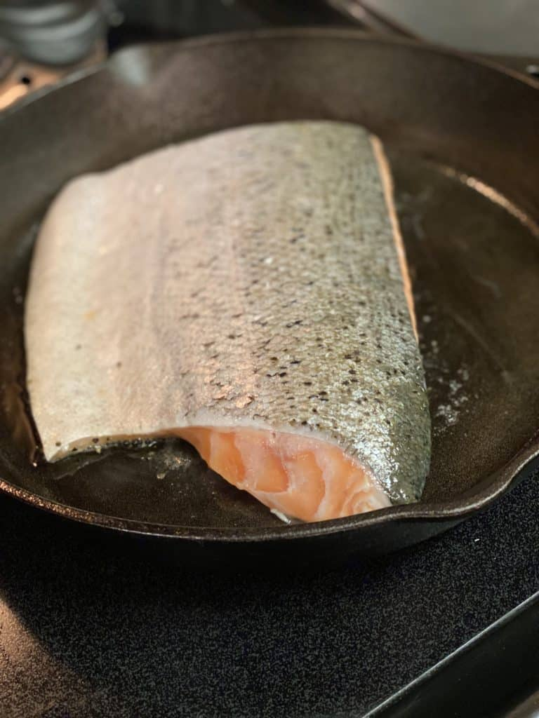 a piece of salmon searing flesh side down in a cast iron pan