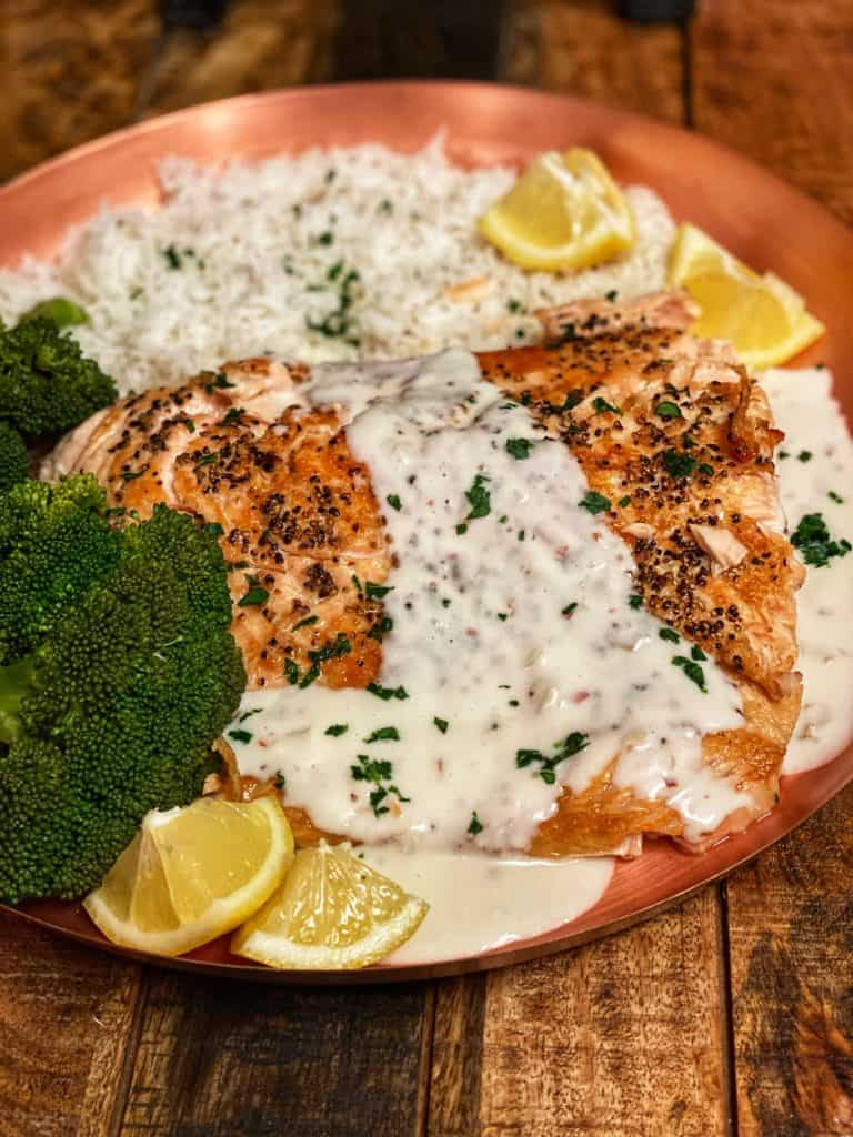 a piece of seared salmon on a copper plate with rice, broccoli and covered in a cream sauce