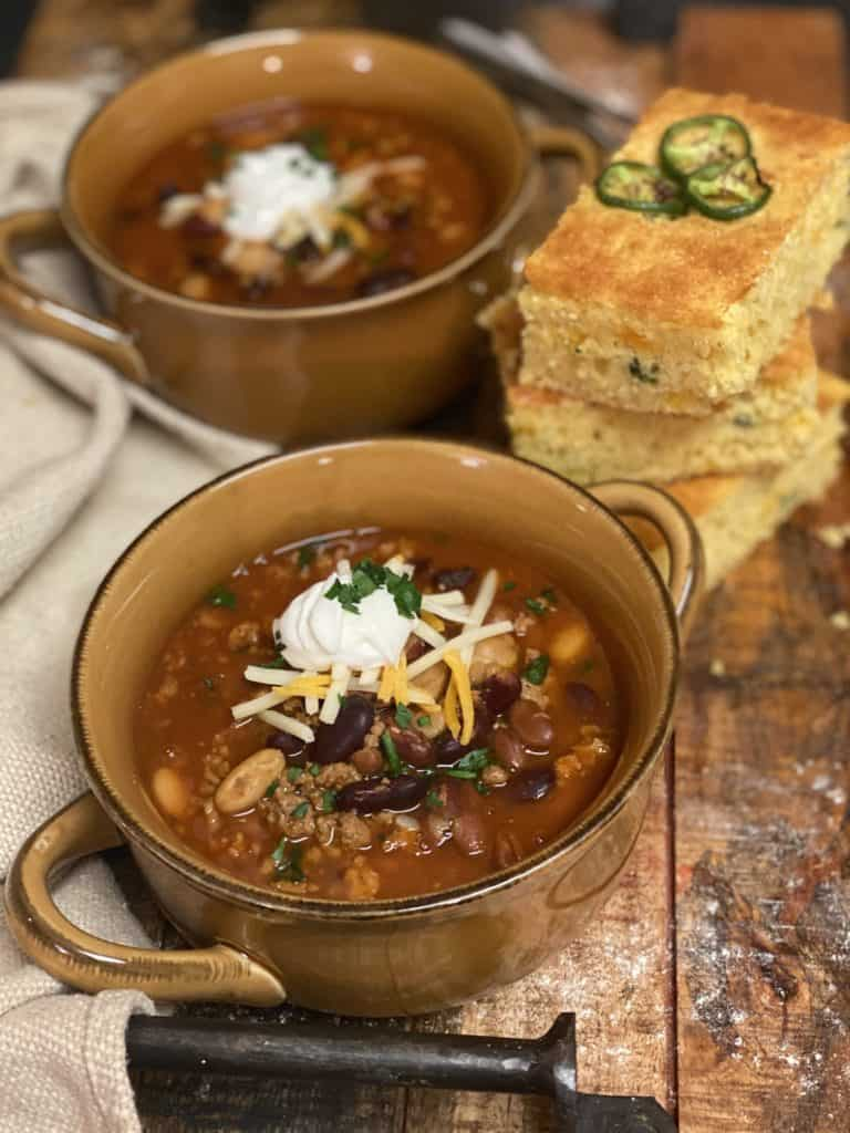 two brown bowls of turkey chili with three slices of jalapeño cheddar skillet cornbread on a wooden board