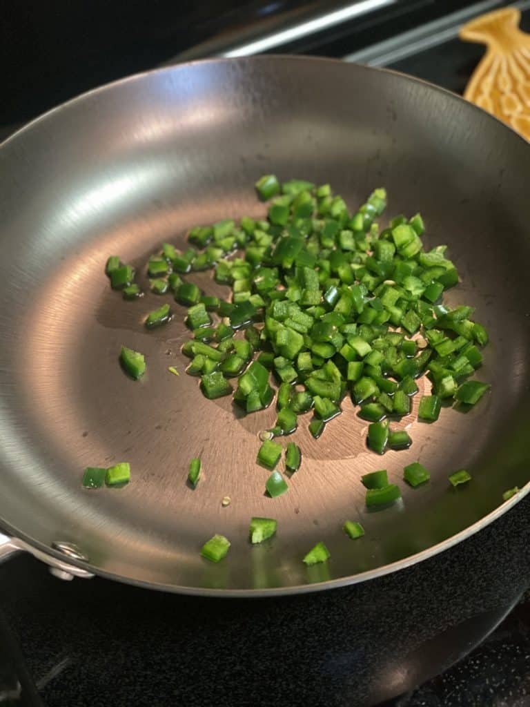 diced jalapeños in a pan with olive oil