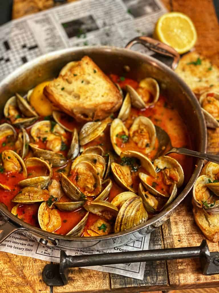 a pan of clams in a chorizo and tomato broth